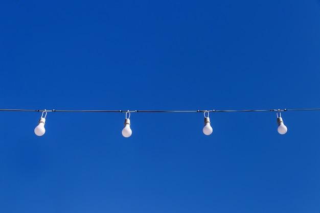 Led-lichtblub in reihe auf blauem himmelhintergrund