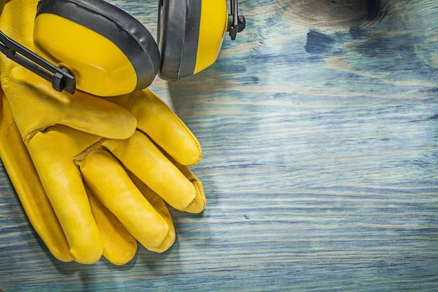 Leder gelbe schutzhandschuhe ohrenschützer auf holzbrettkonstruktionskonzept