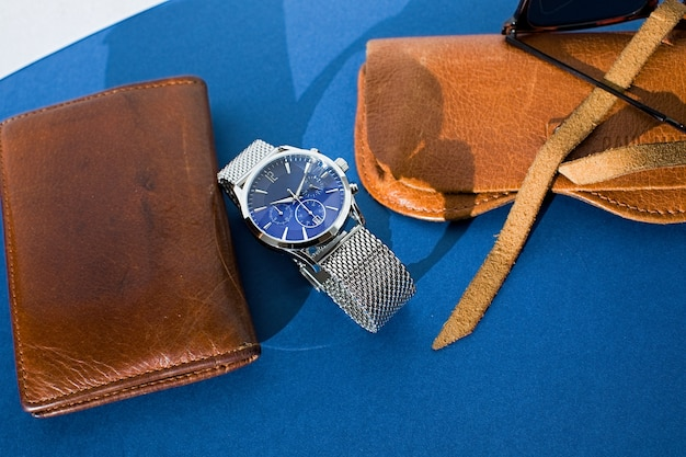 Leder geldbörse, uhr mit einem metallarmband, sonnenbrille und laptop auf blauem hintergrund. zubehör für männer. draufsicht