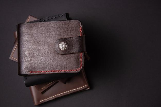 Leder geldbörsen auf einem schwarzen hintergrund mit platz für eine inschrift. lederhandwerk konzept.