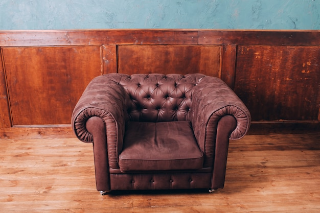 Leder retro sofa im büro. ledersofa auf einem holz. ledersessel mit knöpfen.