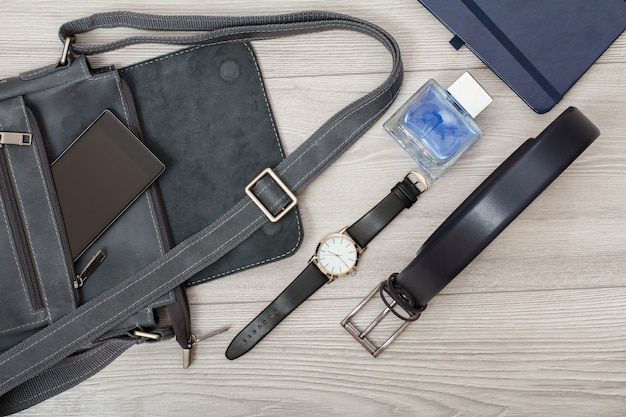 Leder-umhängetasche für männer mit handy drauf, armbanduhr, herren-köln, notizbuch und gürtel für männer mit grauem holzhintergrund. accessoires für herren. ansicht von oben