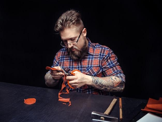 Lederarbeiter, der an seinem arbeitsplatz mit leder mit handwerkswerkzeugen arbeitet.
