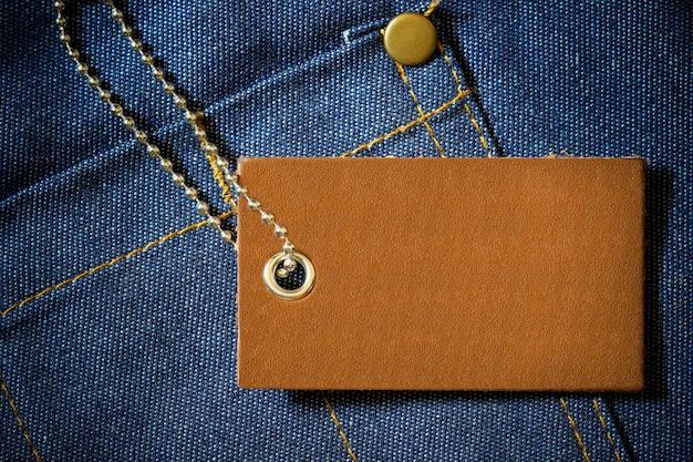Lederetikett mit produktpreis und kugelkette aus edelstahl auf jeanskleidung
