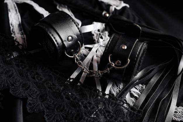 Lederhandschellen und peitsche für bdsm und dienstmädchenkostüm für rollenspiele