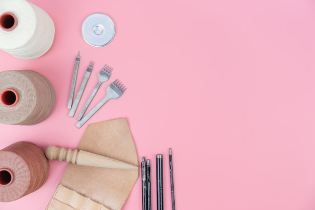 Lederhandwerk werkzeuge gruppe mit gewachstem seil und form punsch auf rosa pastell hintergrund