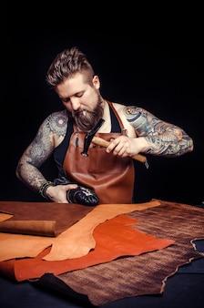Lederhandwerker, der im bräunungsgeschäft neue lederproduktion bildet.