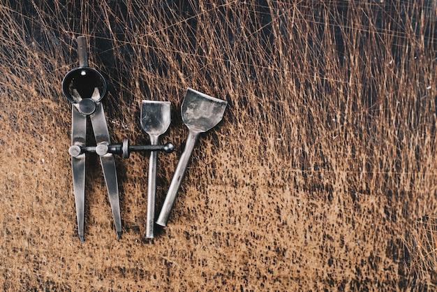 Lederhandwerkwerkzeuge auf einem hölzernen hintergrund. leder craftsman schreibtisch
