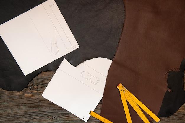 Lederlineal und zeichnungen werden auf den tisch gelegt