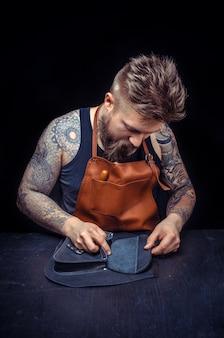 Ledermeister arbeitet als handwerker in seinem arbeitsregal.