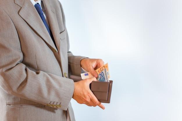 Lederne geldbörse mit geld in den geschäftsmannhänden auf weiß