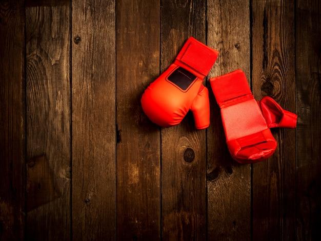 Lederne karatehandschuhe auf dem hölzernen hintergrund. ansicht von oben