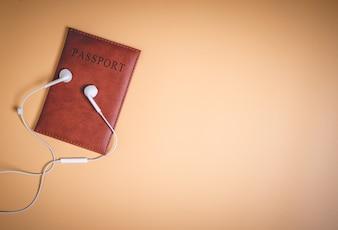 Lederner brauner Pass mit weißen Kopfhörern auf braunem Kopienraum
