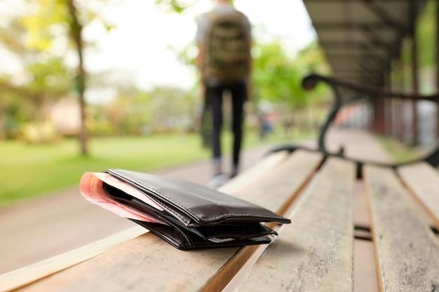 Lederner geldbeutel mit einem geld, das auf der parkbank liegt, während touristen weg gehen. - bild