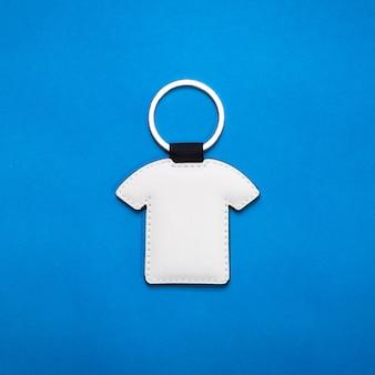 Lederner schlüsselring in der hemdform auf hintergrund des blauen papiers