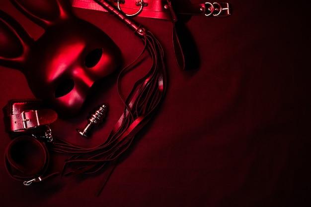 Lederpeitsche, handschellen, halsband, maske und metall-analplug für bdsm-sex mit unterwerfung und dominanz