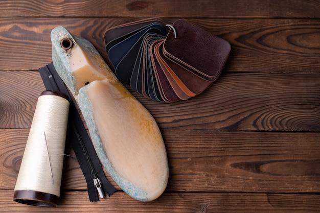 Lederproben für schuhe und plastikschuh dauern auf dunklem holztisch