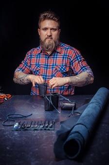 Lederschneider, der mit leder mit handwerkszeugen im bräunungsgeschäft arbeitet
