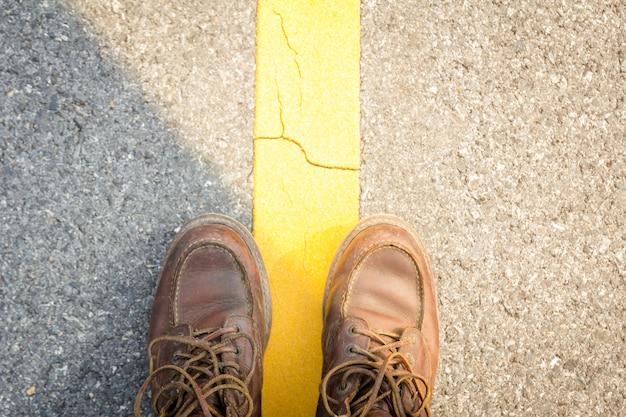 Lederschuhe nahe gelber straßenlinie