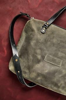 Ledertasche aus grauem leder, handgefertigt auf einem stück bordeauxrotem leder, nahaufnahme.