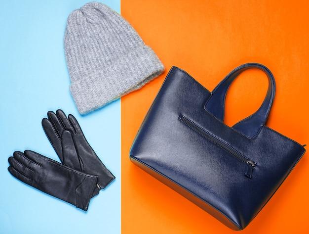 Ledertasche, handschuhe, wollwintermütze auf zweifarbigem neonhintergrund