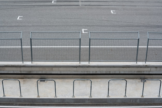 Leer asphaltstraßen-rundkurs und schutzzaun mit startposition ansicht von der tribüne.