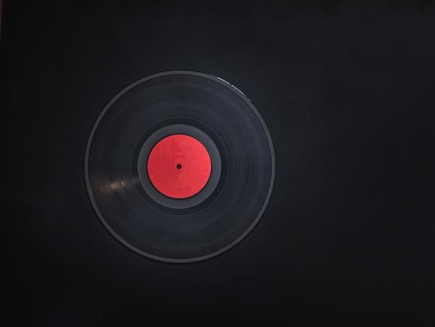 Leere abstrakte vinylaufzeichnung ohne text auf schwarzer dunkler oberfläche mit kopienraum
