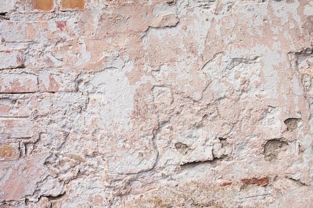 Leere alte backsteinmauerbeschaffenheit. bemalte grungy wandoberfläche. grunge roter steinmauerhintergrund. schäbige gebäudefassade mit beschädigtem putz.