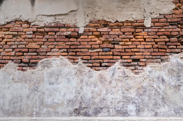 Leere alte backsteinmauerbeschaffenheit. mauerzerfall siehe roter backstein. gebäudefassade mit beschädigtem gips.