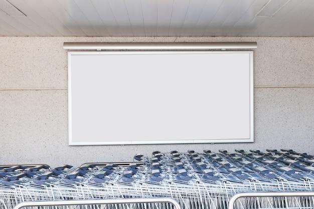 Leere anschlagtafel für reklameanzeige auf betonmauer mit laufkatzengepäck im flughafen