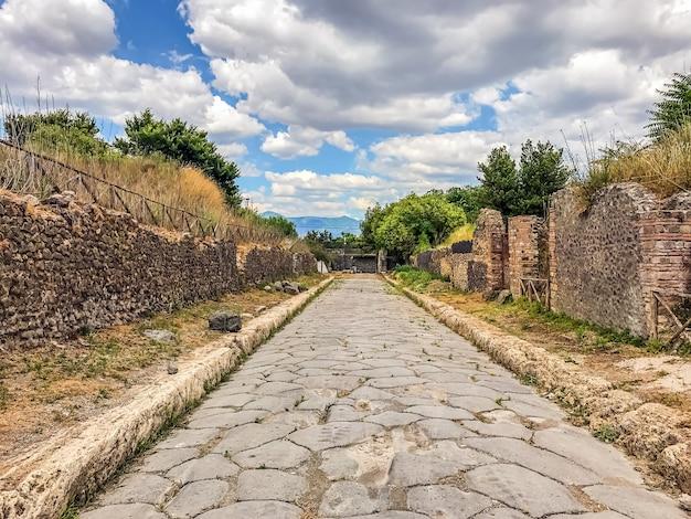 Leere antike römische stadt von pompeji unter einem blauen himmel mit wolken. panorama einer verlassenen straße in pompeji.