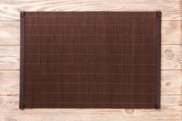 Leere asiatische küche. dunkle bambusmatte auf draufsicht des braunen hölzernen hintergrundes mit copyspace ebenenlage