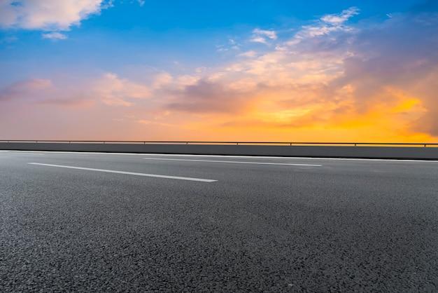 Leere asphaltstraße und naturlandschaft in der untergehenden sonne