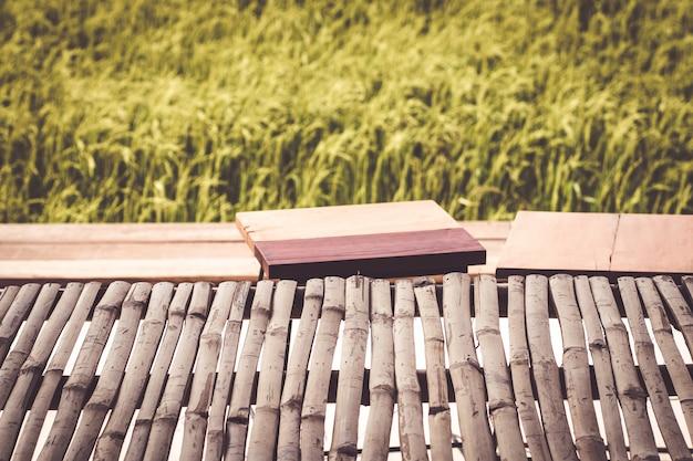 Leere bambustabelle für produktanzeigenreisfeldunschärfehintergrundnaturumweltlebensstil-konzeptidee