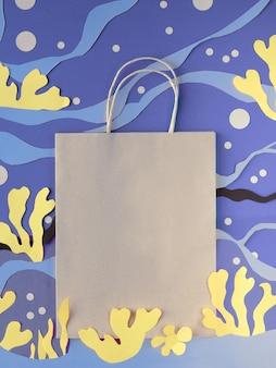 Leere bastelpapiertüte auf abstraktem unterwasserhintergrund aus geschnittenem papier. matisse-inspirierte collage-anordnung zum schneiden von papier.