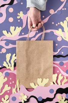 Leere bastelpapiertüte auf abstraktem unterwasserhintergrund des meeres. von matisse inspirierte collage aus papierkunst.