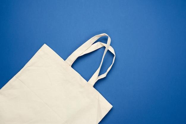 Leere beige textiltasche auf blauem hintergrund
