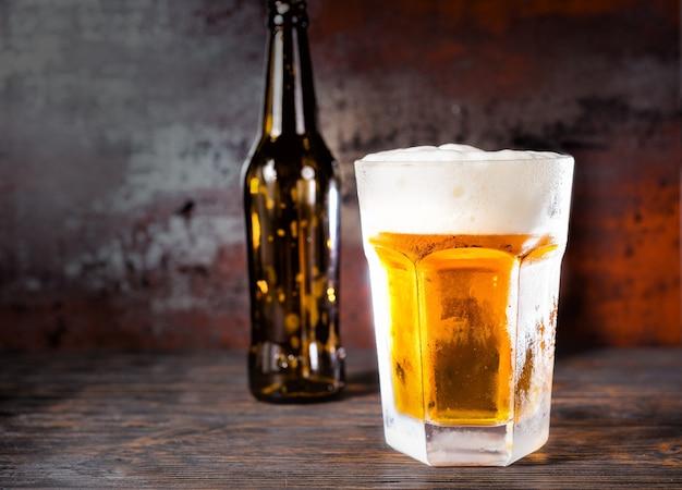 Leere bierflasche neben glas mit einem hellen bier und einem schaumkopf auf altem dunklem schreibtisch. getränke- und getränkekonzept