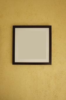 Leere bilderrahmen auf gelben wänden der weinlese.