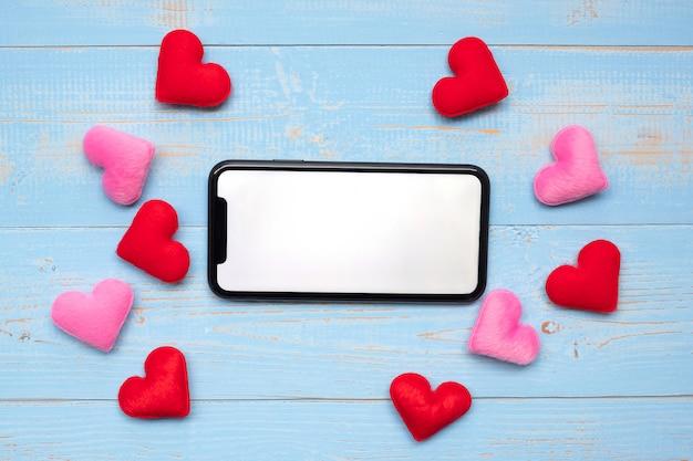 Leere bildschirmanzeige des schwarzen intelligenten telefons mit den roten und rosa herzen formen dekoration auf blauem holztischhintergrund.