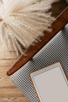 Leere bildschirmtablette auf vintage-stuhl. flache lage, minimalistisches blog mit draufsicht, website