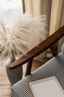 Leere bildschirmtablette auf vintage-stuhl. minimalistischer blog, website