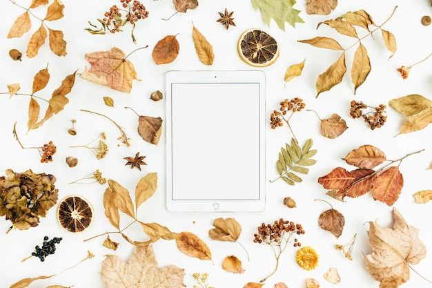 Leere bildschirmtablette mit trockenem herbstherbstblatt, blütenblättern und orangen auf weißer oberfläche