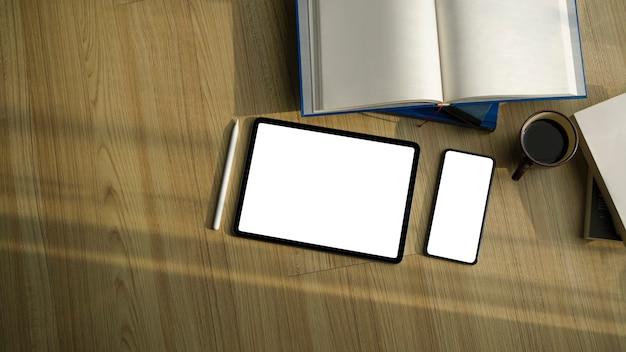 Leere bildschirmtablette und smartphone mit büchern auf holzboden.