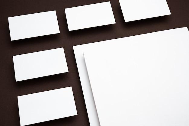 Leere blätter, die über braunem hintergrund schweben, kreativ. weiße karten. modernes mockup im bürostil für werbung. leeres weißes exemplar für design-, geschäfts- und finanzkonzept.