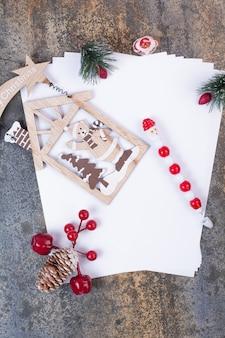 Leere blätter mit weihnachtsdekoration auf marmorfläche.