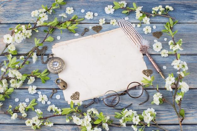 Leere blätter, taschenuhr, herzen, vorhängeschloss, schlüssel, füllfederhalter und kirschblüten