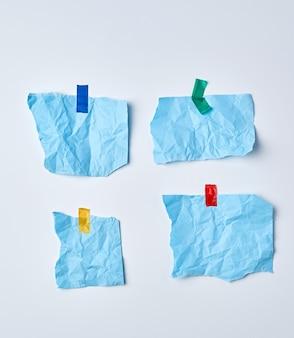 Leere blau zerknitterte papierstücke werden mit klebeband verklebt