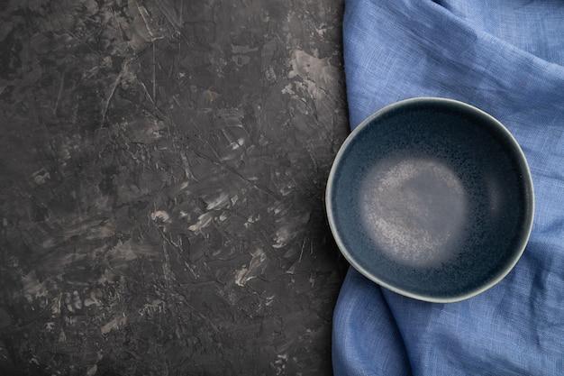 Leere blaue keramikschale auf schwarzem betonhintergrund und blauem leinentextil
