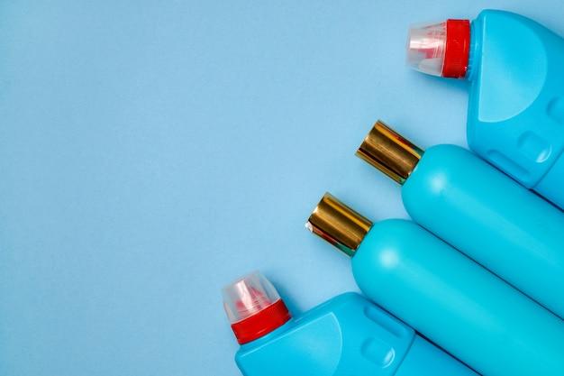 Leere blaue plastikflaschen im hintergrund des rechten teils. haushaltschemie, shampoo, reiniger.
